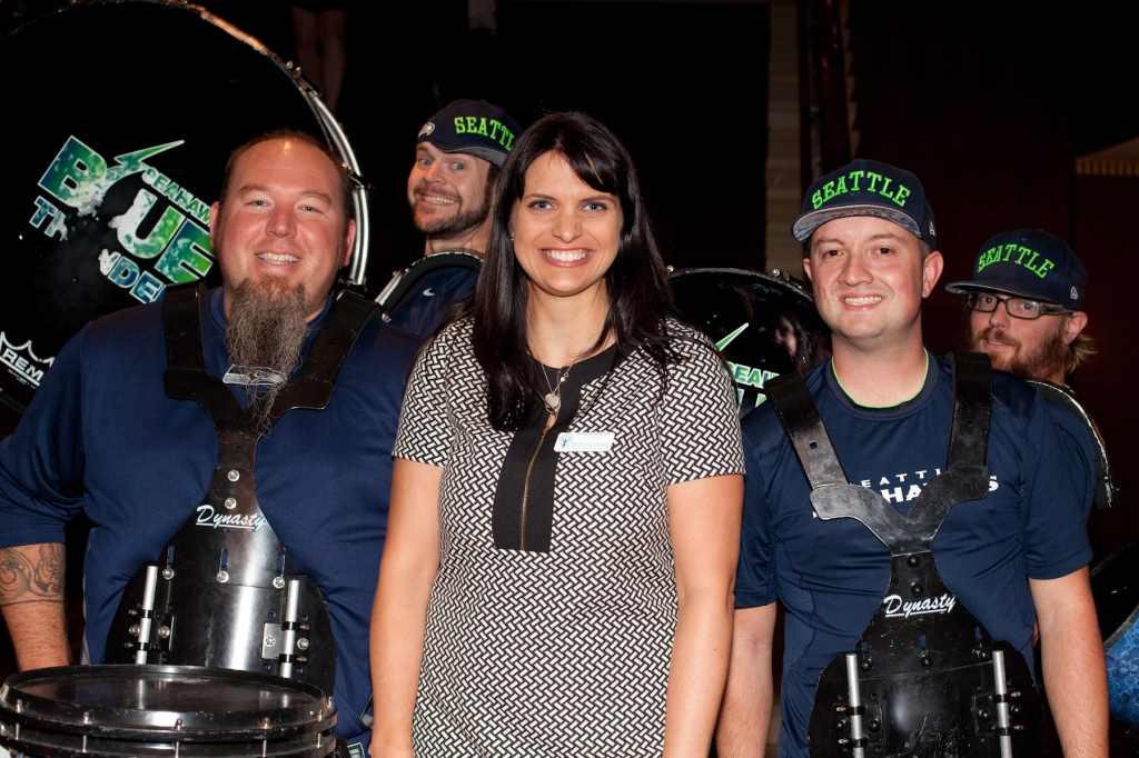 Rebecca Wilson, President of the Junior League of Seattle, with members of the Seahawks Blue Thunder drum line.